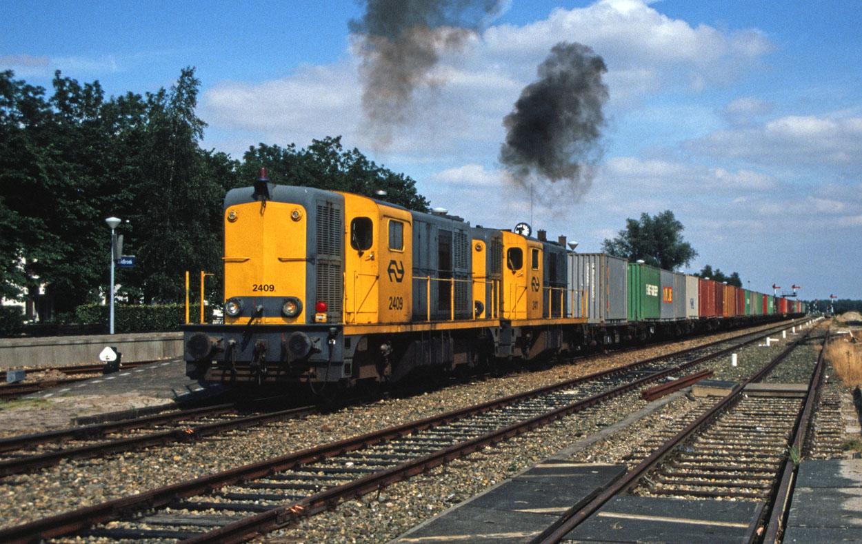 NS 2409 and 2411 accelarate out of Zuidbroek (NL) with a container train from Veendam (NL) to Maasvlakte (NL) in the summer of 1989.