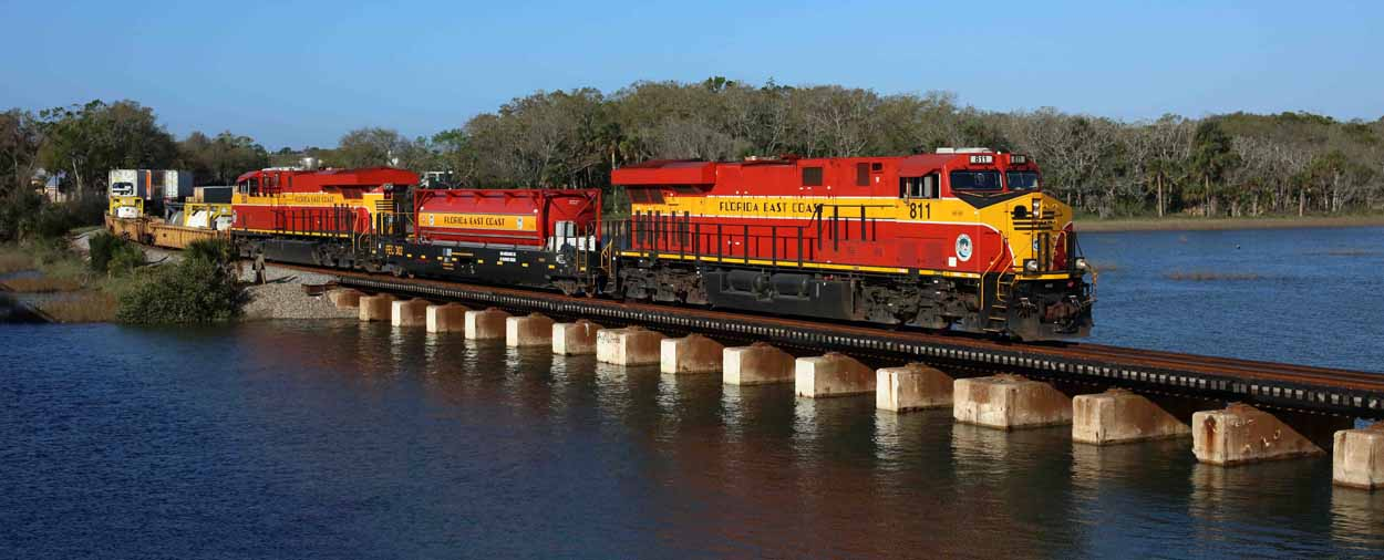 Florida East Coast Railway 811 and 803 sandwich FEC LNG tender 302, taking northbound intermodal train 226 (Hialeah Yard - Bowden Yard) across the San Sebastian River on 11 March 2017.