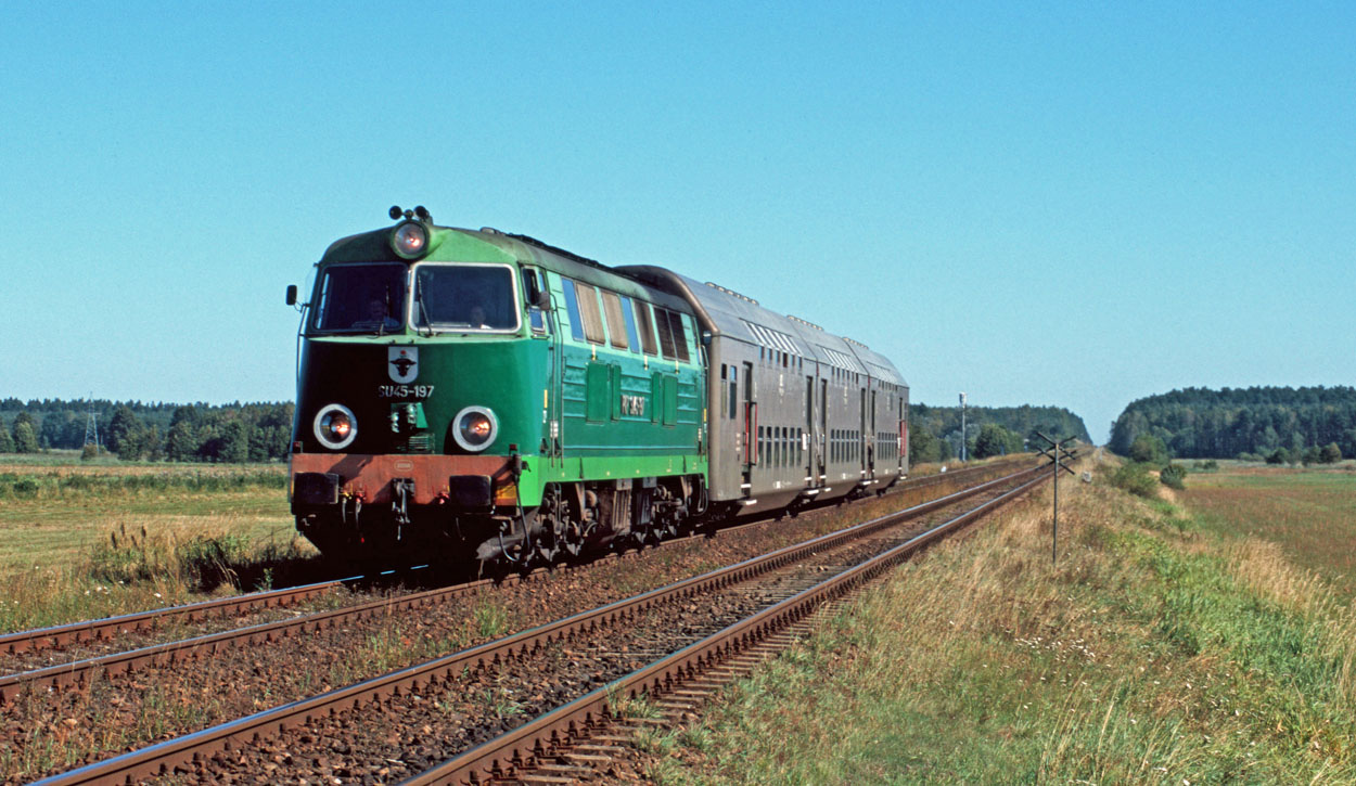 PKP SU45-197 takes a rake of three double-deck coaches as train 58833 from Tczew (PL) to Chojnice (PL) at Czarna Woda (PL) on 10 September 2004.