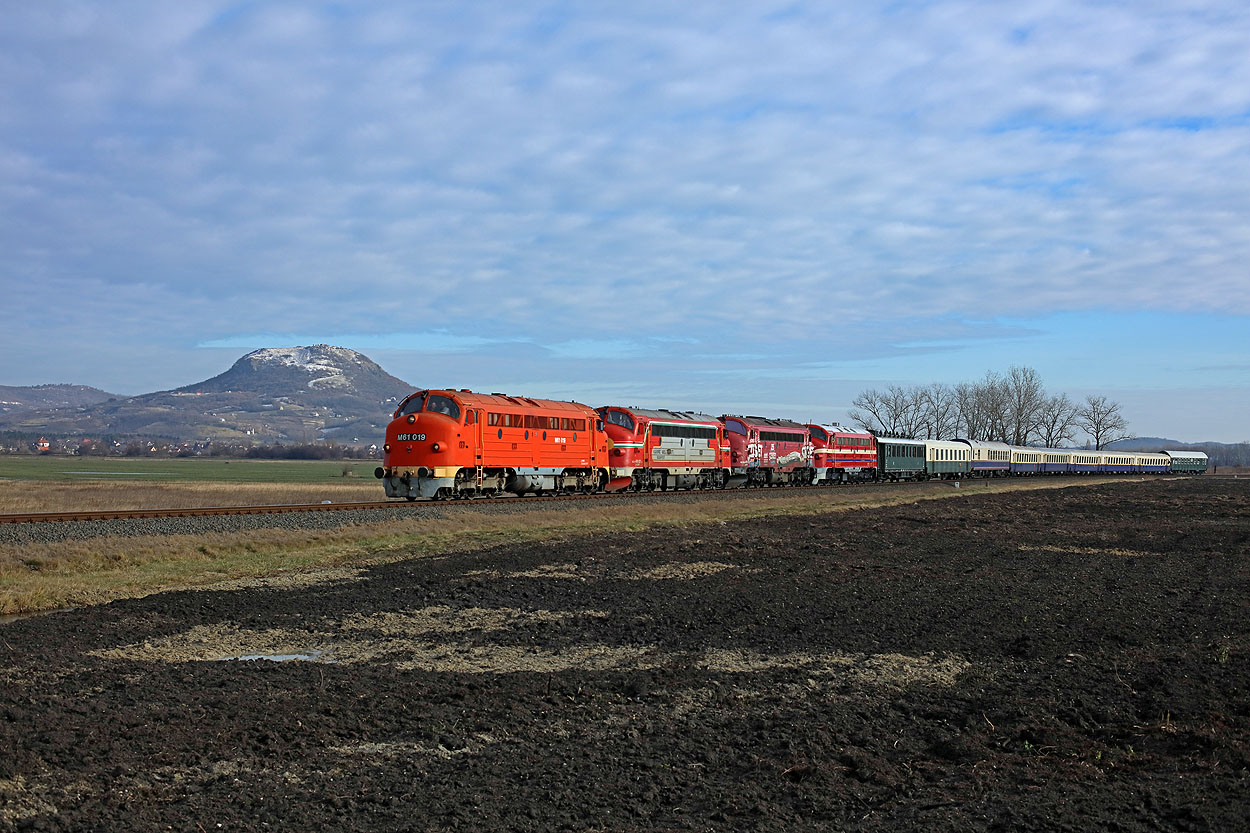MNOS M61.019 + KV 459.021 + KV 459.022 + MAV M61.017 + 9 MNOS coaches (train Vulkan from Budapest Kelenfold to Tapolca via Aszofo) pass an expired vulcano at Tapolca on 30 December 2017.